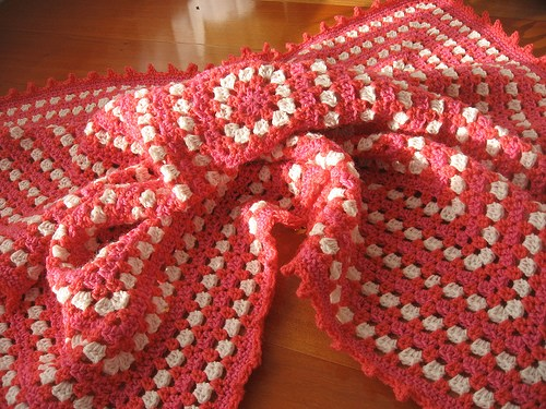 Crocheted red and white granny square blanket on a wooden surface