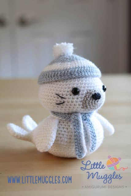 Crocheted white seal with a blue scarf and hat on a beige wooden surface that looks like a table