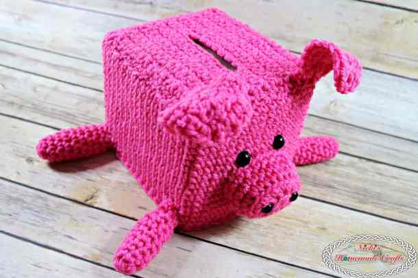 Crocheted pink Piggy Bank Tissue Box Cover sitting on wooden surface