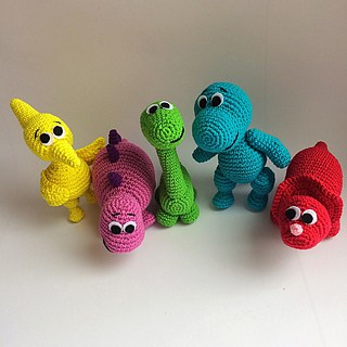 Crocheted Yellow, pink, green, blue and red dinosaur on a white background and surface