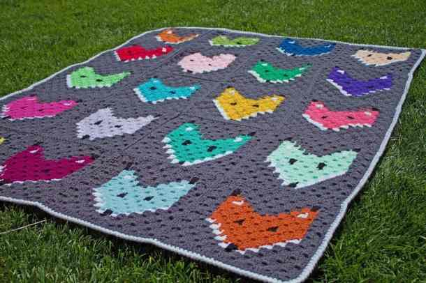 Crocheted colorful corner to corner blanket with foxes on it each having a different color, laying on a grass surface