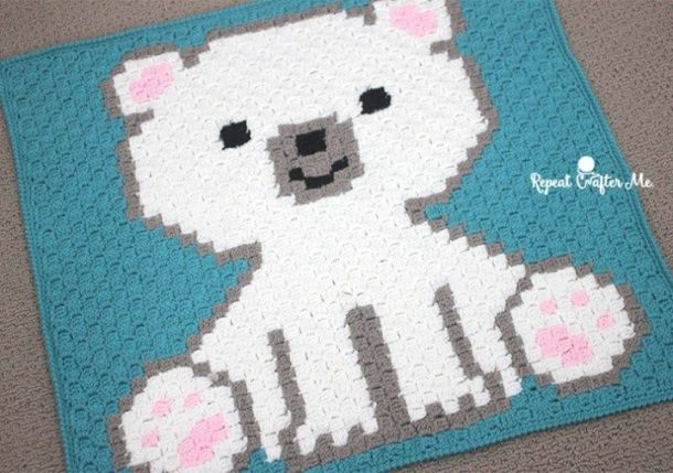 Crocheted Corner to Corner blue blanket with white polar bear that has pink feet and ears