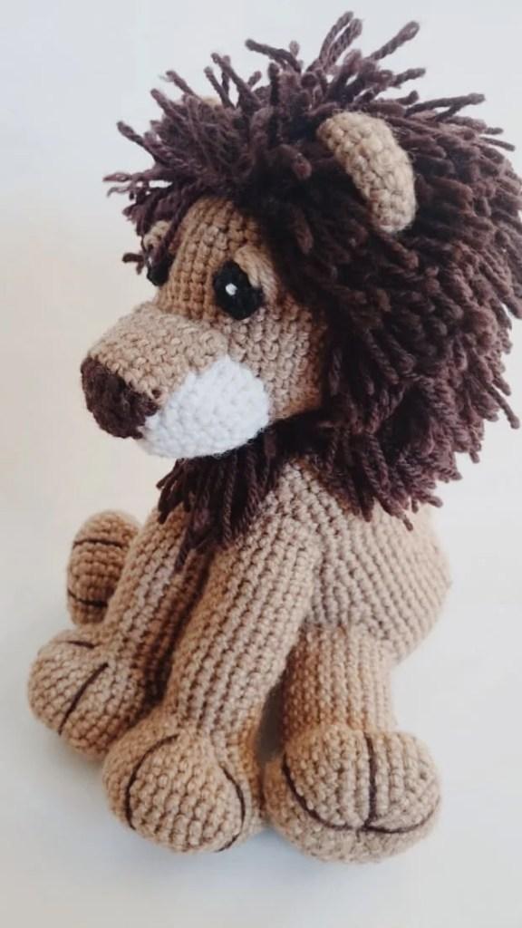 Crocheted brown Lion sitting sadly on white surface