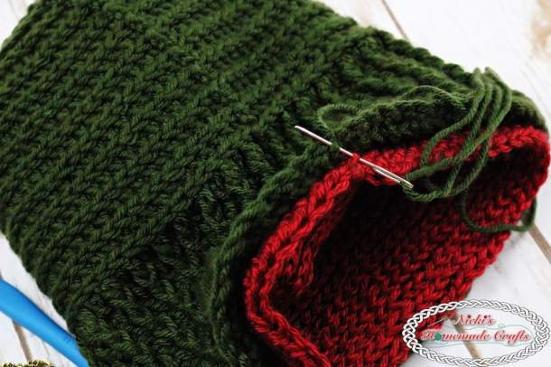 The beanie is being sewn up using a tapestry needle. The beanie is green and red and has vertical and horizontal lines.