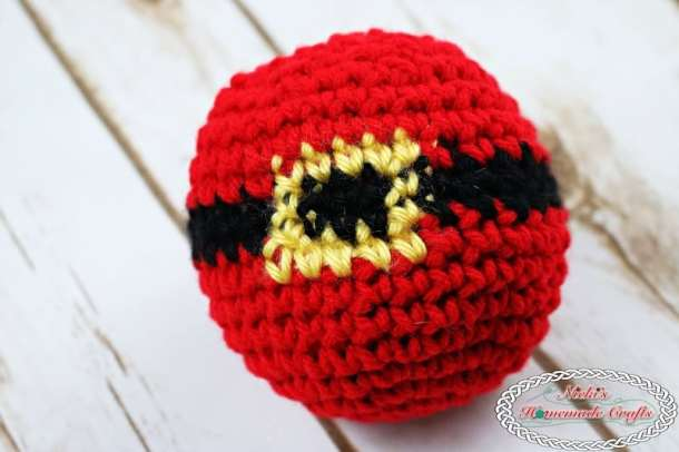 Santa Belt Christmas Ornament - entire ornament without the hanger shown lying on wood floor ready to be glued to the hanger for the christmas tree - Free Crochet Pattern by Nicki's Homemade Crafts #crochet #ornament #christmas #winter #tree #free #crochet #pattern #belt