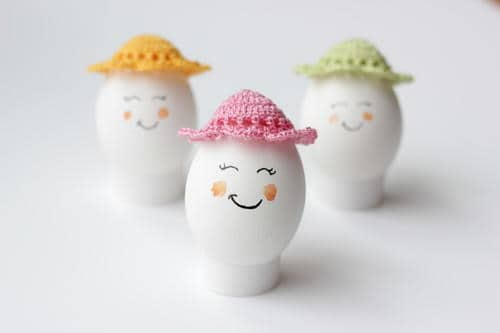 Easter Egg Bonnets in colors green, yellow and pink displayed on smiling easter eggs on a white stand that are on a white surface.