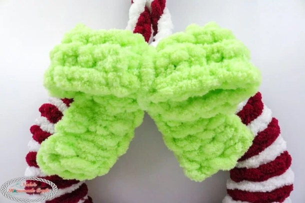 green bow on red and white loop yarn wreath