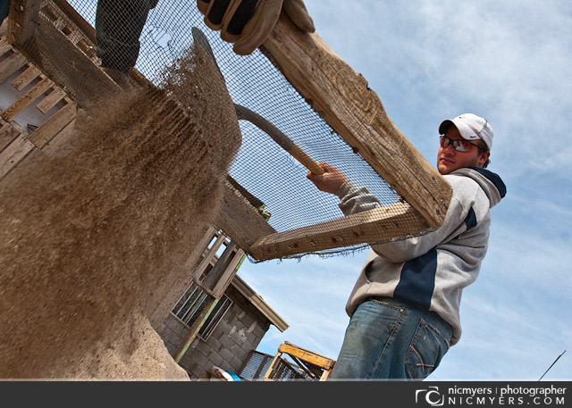 Juarez, Mexico. Sifting sand for stucco.