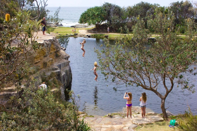 People jumping from the rocks at the Blue Pools in Angourie, NSW, Australia