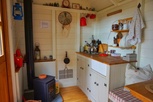 The kitchen with log burner inside the shepherd's hut at Warmwell House.