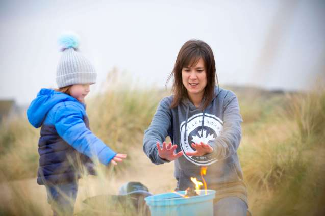 Emily and I warming our hands up over the camp fire during our photo shoot for Westbeach clothing company