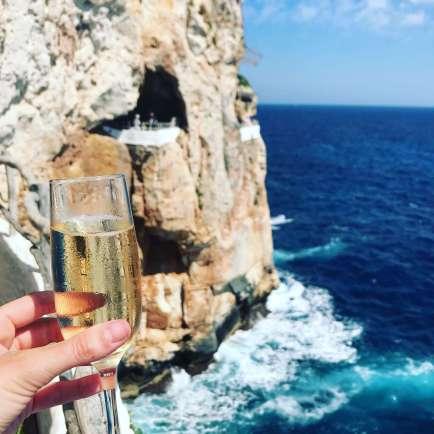 A glass of Prosecco in hand at Cova d'en Xoroi, Menorca.
