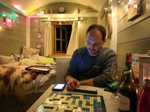 Matt playing scrabble in the shepherd's hut, Warmwell, Dorset