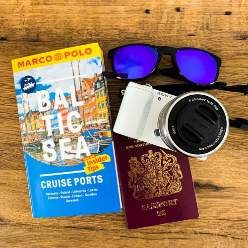 A flat lay image of my travel must haves: Baltic Sea Ports Marco Polo Travel Guide, sunglasses and camera