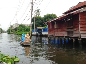 Unique views of Bangkok on the Chao Phraya River. Two ladies in a boat and houses on stilts