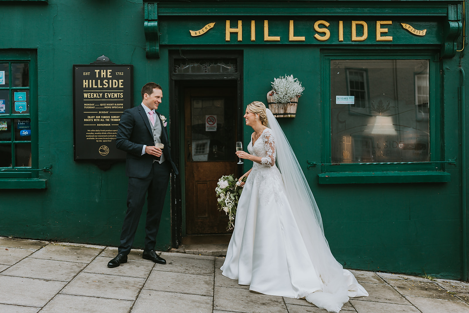 Bride and Groom haing a pint of Guinness outside of an Irish pub