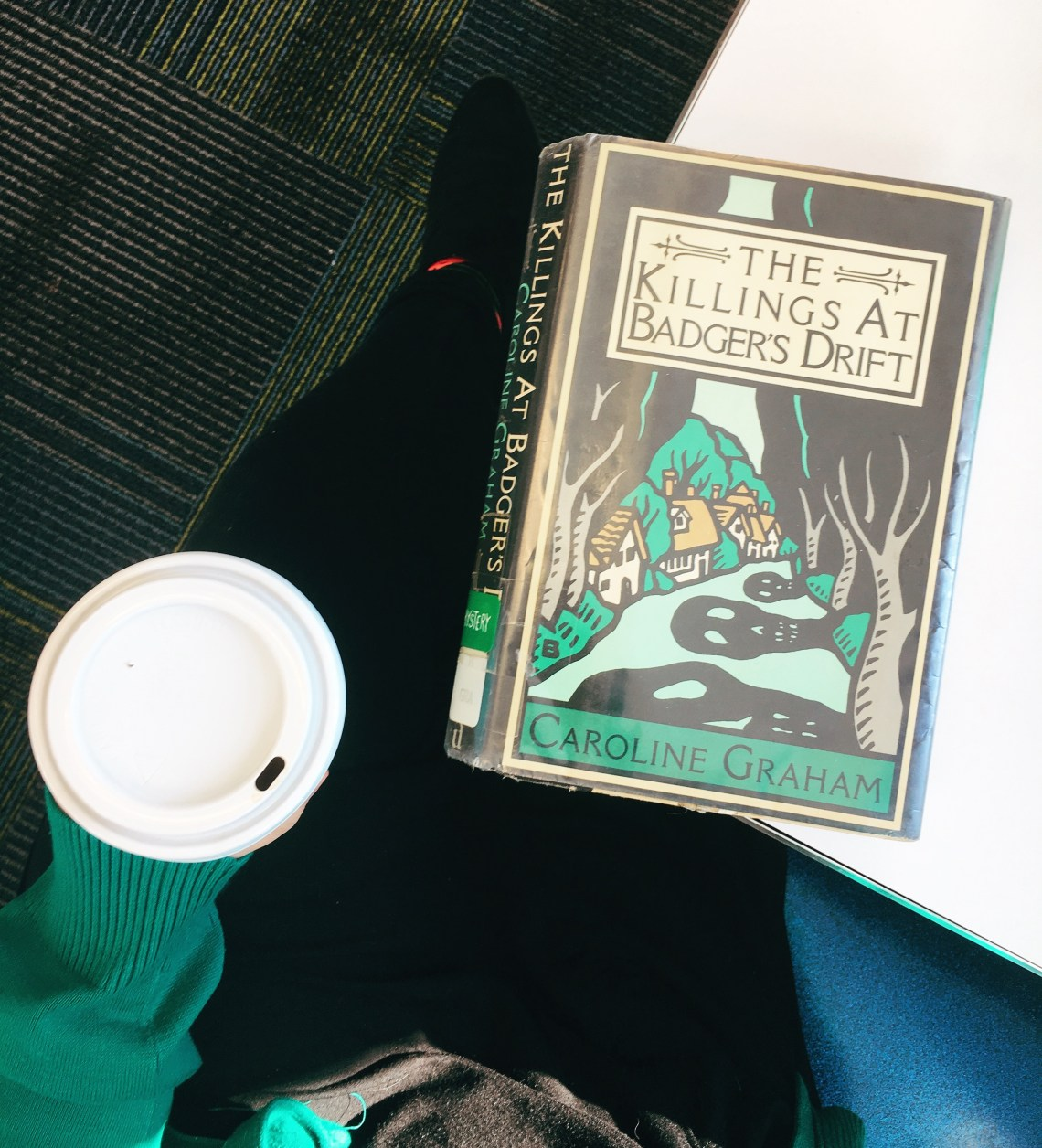 Shot of me holding coffee while a copy of the book lies on a tabletop