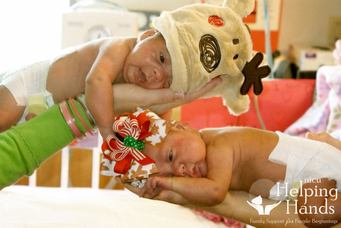 Two newborns in the NICU wearing special holiday outfits.