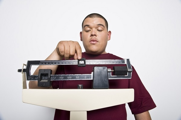 Photo of young man weighing himself - La diabetes Tipos y prevención de enfermedad