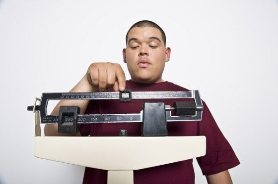 Photo of a young man weighing himself