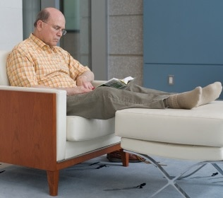 Photo of a man sitting reading a book with his feet resting on footstool.