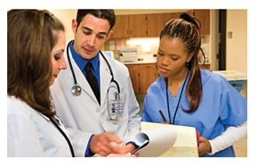 A doctor, nurse, and technician review test results in a clinic.