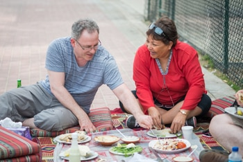 Man and woman having picnic lunch outside
