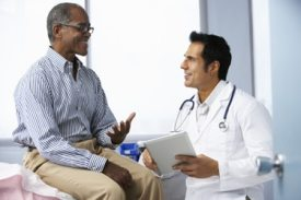 Male doctor talking to male patient sitting on an examining table.