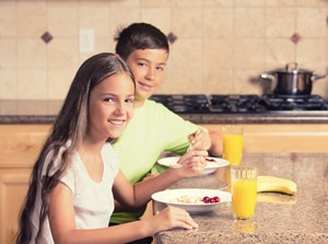 Photo of boy and girl sitting at kitchen counter eating breakfast