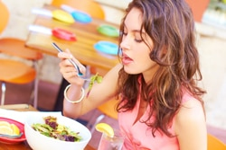 Girl eating a salad and drinking water with lemon.