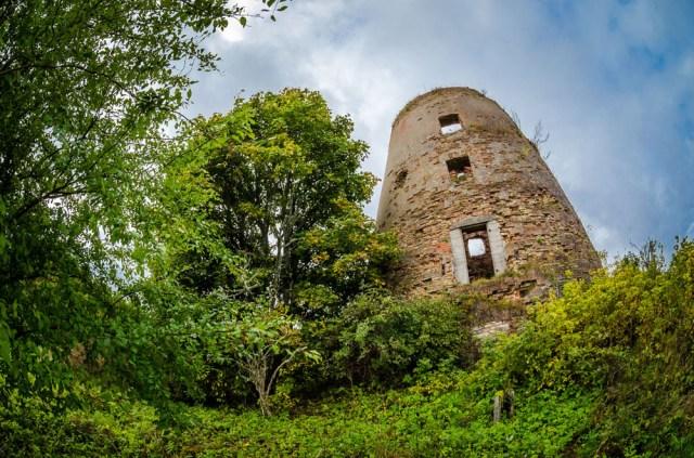Kiek atokiau, kaimo pakraštyje stovi senai nebenaudojamo vėjo malūno mūrai