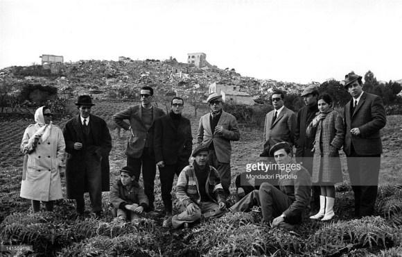 Grupelė išgyvenusių drebėjimą savo miestelio fone. Salaparuta. 1968 m.