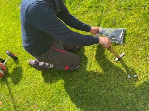 Die Sensor-Schiene für den Rasenroboter wird gelegt.