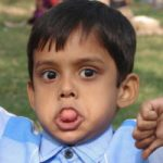 Jongen die zijn tong uitsteekt. Copyright foto: Manosh Sengupta