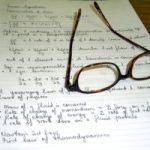 Handgeschreven aantekeningen van een student, met een bril er bovenop. Copyright foto: Jenny Rollo