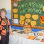 Leerkracht in pompoenenvest voor een schoolbord vol pompoenen, les over Halloween! Copyright foto: Loretta Humble