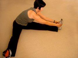 Vrouw doet stretchoefening voor het sporten. Copyright foto: Lotus Head