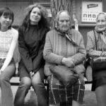Een paar jongedames en oudere dames zitten samen op een bankje. Copyright foto: Yarik Mishin
