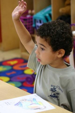 Kind steekt zijn hand op in de klas om iets te vragen: hoe zit het nou? Copyright foto: Anissa Thompson