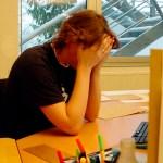 Persoon aan een bureau die het niet meer ziet zitten en met de handen voor het gezicht zit. Copyright foto: Carl Dwyer
