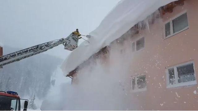 Operarios retiran los metros de nieve de los tejados en Ramsa am Dachstein
