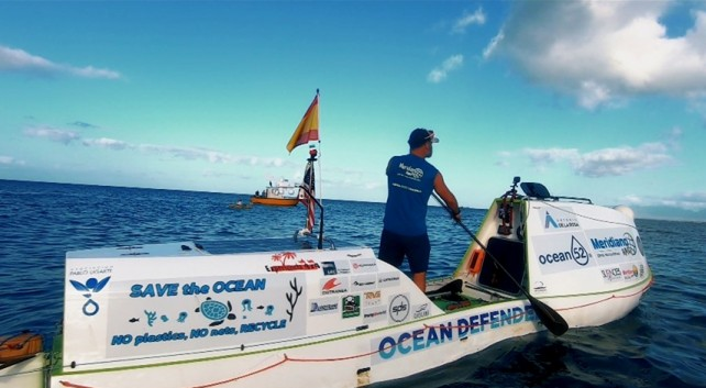 "El navegante sobre su paddle con el lema ""Save the Ocean"""