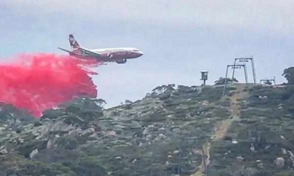 Un avión descarga líquido retardador del fuego sobre Perisher Valley. FOTO: @charlottepass
