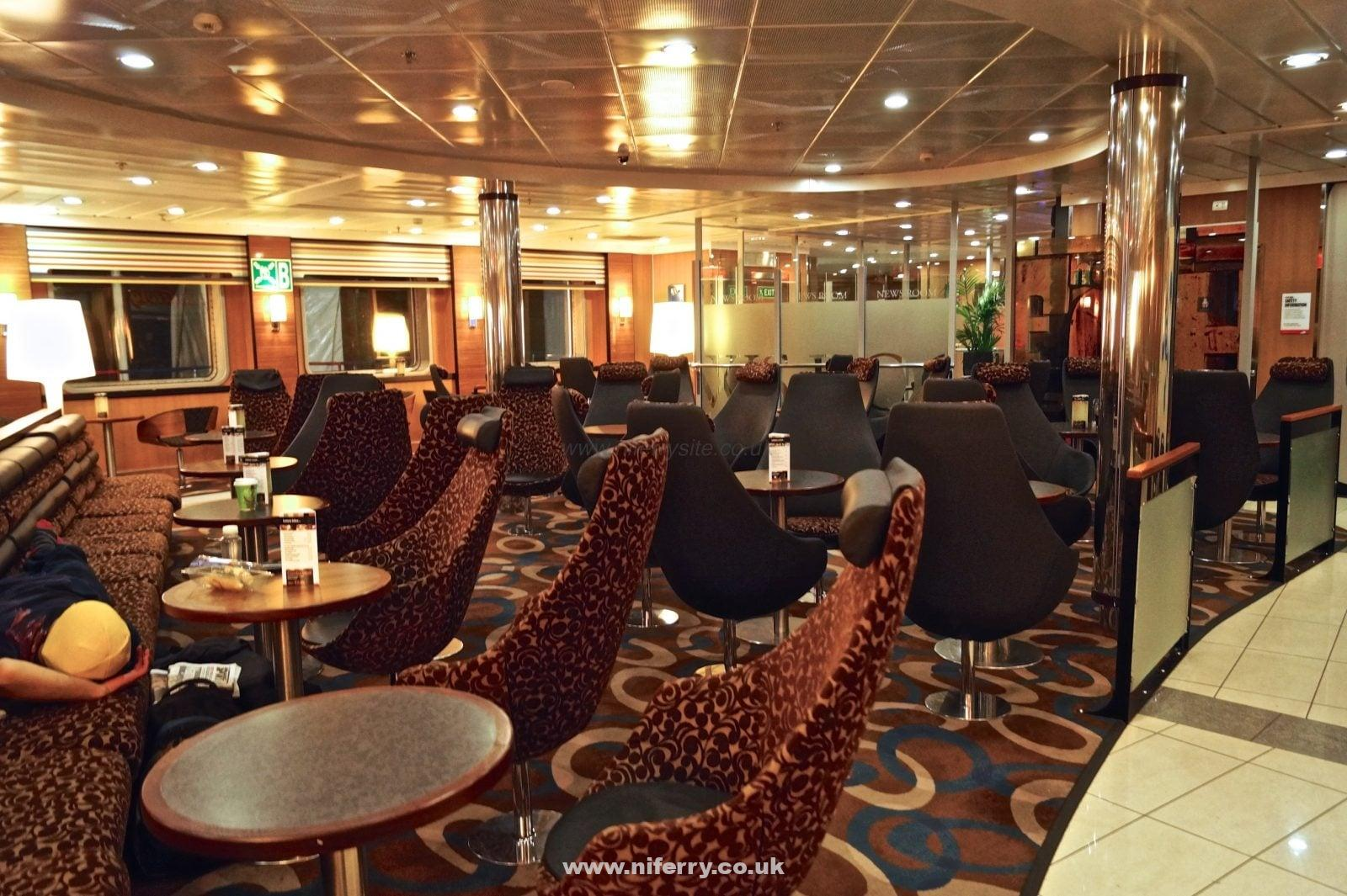 Continuing our walk towards the bow (front) of the ship, we next pass through one of the main seating areas, the Barista Coffee Shop. This view is taken from the other side looking towards the news room (the glass panels in the background). © NIFerrySite.