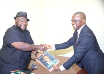 The Author of the Book the Memoirs of a Journalist in a Government Media, Sir Fidelis Egwugbo (right), presenting a copy of his Book to the Chairman, Delta State Library Board, Dr Israel Abido in his office, Asaba. PIX: BRIPIN ENARUSAI