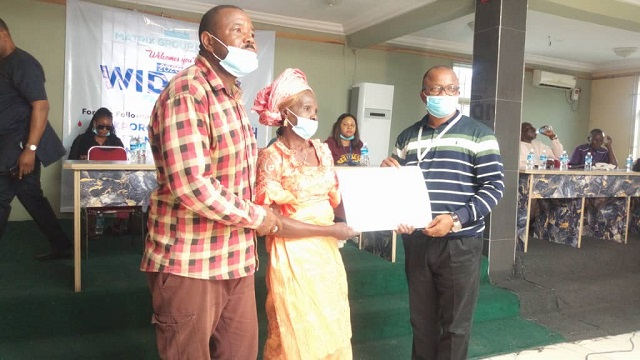 One of the widows receiving her cheque from Mr. Fred Olomuro who represented the Chief Operating Officer of Matrix Energy Limited at the empowerment ceremony for 67 widows in Delta State