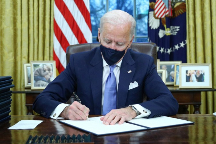 U.S. President Joe Biden signs executive orders in the Oval Office of the White House in Washington, after his inauguration as the 46th President of the United States, U.S., January 20, 2021. REUTERS/Tom Brenner