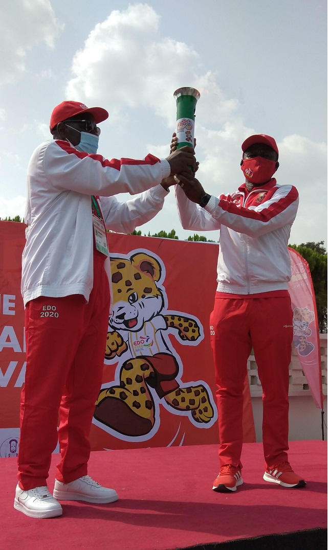 Obaseki handing over the torch to the chairman of the LOC, Philip Shaibu