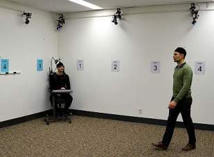 Picture of volunteer epilepsy patient sitting in corner of experimental room, wearing a special brain wave monitoring backpack and watching another participant search for a hidden spot. The other participant is shown walking.