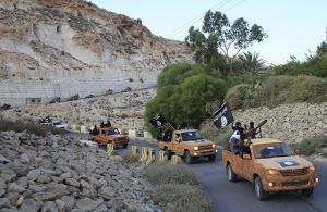 「イスラム国」の黒旗を掲げるリビアの過激派(リビア東部デルナ)=ロイター